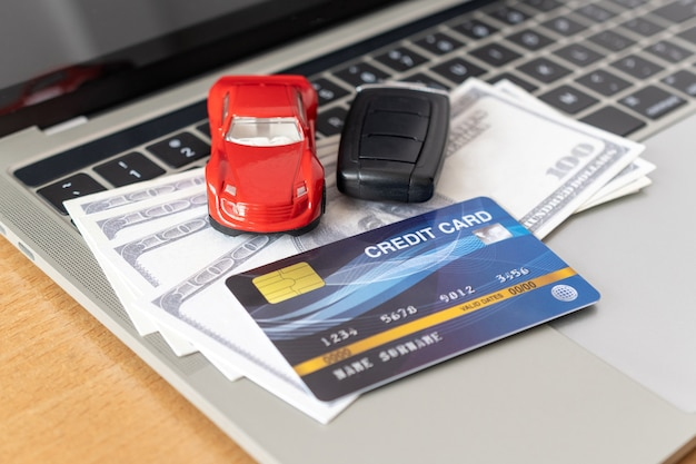 Carta di credito, modello di auto e taccuino sulla scrivania in legno. acquisti online e pagamento in auto utilizzando il laptop