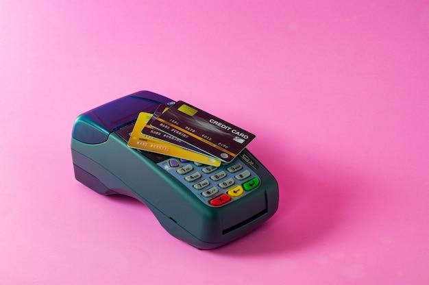 Scanner per carte di credito e carte di credito su sfondo rosa