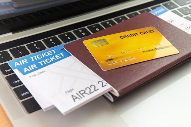 Carta di credito e passaporti vicino al computer portatile sul tavolo. concetto di prenotazione di biglietti online
