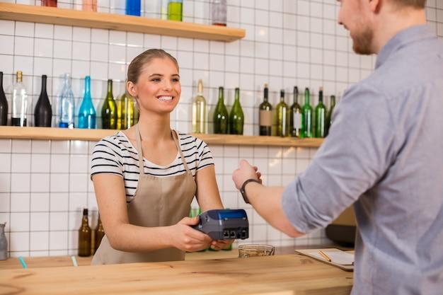 Pagamento con carta di credito. donna attraente piacevole allegra che sorride e che utilizza un terminale della carta mentre prende il pagamento dal cliente