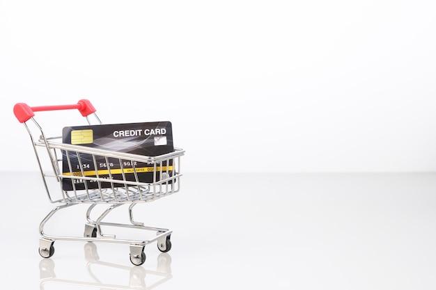 Carta di credito nel carrello per lo shopping online su bianco, concetto di lavoro da casa