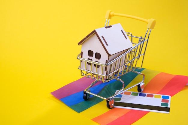 Carta di credito, piccola casa in un carrello della spesa sulla bandiera della comunità lgbt, sfondo giallo, luogo di copia