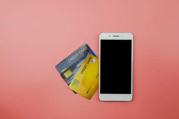 Carta di credito e smart phone con copia spazio su sfondo rosa chiaro, vista dall'alto