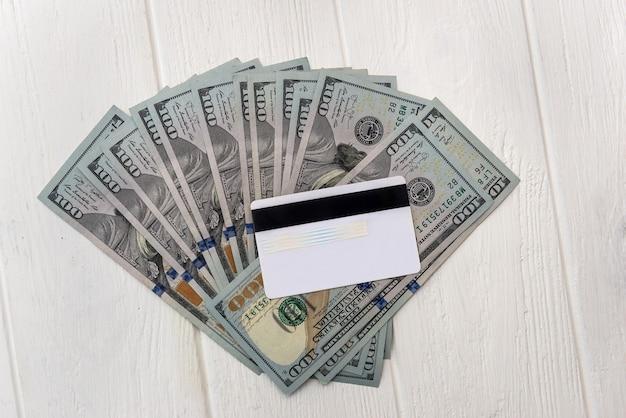 Carta di credito con banconote in dollari sul tavolo