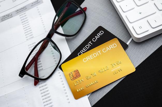 Carte di credito, calcolatrice, bollette e bicchieri