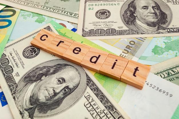 Iscrizione di credito su cubi di legno sulla trama di dollari americani e banconote in euro