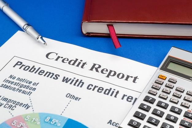 Rapporto di credito sul tavolo blu, penna, taccuino e calcolatrice.