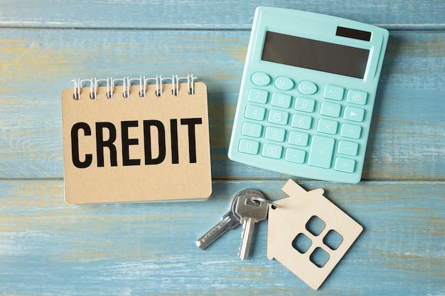 Blocco note texton di credito con chiavi e calcolatrice sulla tavola di legno