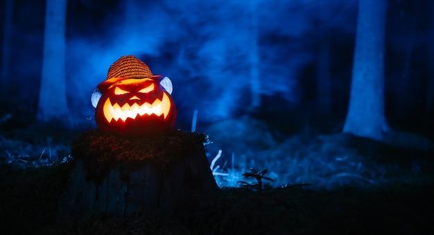 Zucca scolpita inquietante per halloween con fumo blu sullo sfondo di un concetto di foresta oscura holid...
