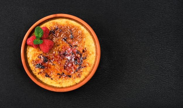 Crème brulée dessert con panna e zucchero di canna con lamponi e foglie di menta su un tavolo scuro, layout con copia spazio. deliziosi dolci fatti in casa