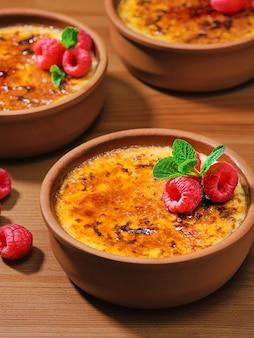 Creme brulee dessert con panna e zucchero di canna con lamponi freschi e foglie di menta in ciotole di argilla su un tavolo vintage scuro, close-up con messa a fuoco selettiva.
