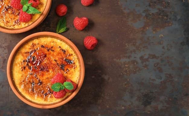 Creme brulee dessert con panna e zucchero di canna con lamponi freschi e foglie di menta in ciotole di argilla su un tavolo vintage scuro, mock up con lo spazio della copia. deliziosi dessert in un bar o in un ristorante