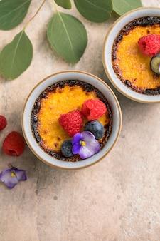 Creme brulee. dessert francese alla crema alla vaniglia con zucchero caramellato e frutti di bosco, fuoco selettivo.