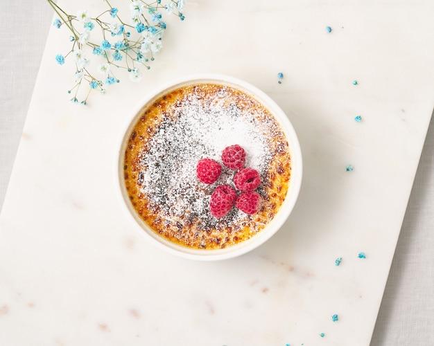 Crème brulée tradizionale francese crema alla vaniglia dessert con zucchero a velo e lampone