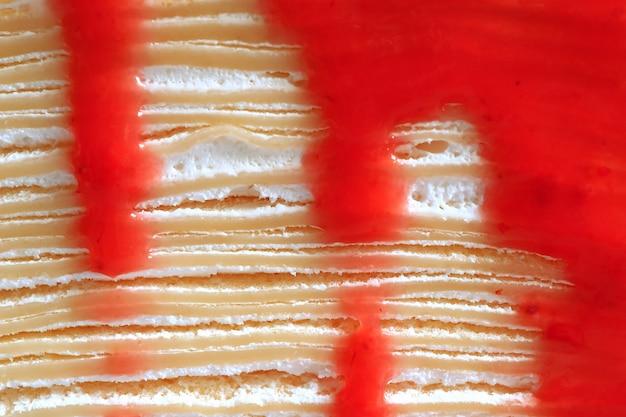 Strati di torta di crepe con salsa di lamponi rosso vibrante e crema fresca
