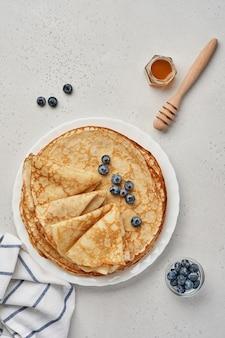 Crepes, frittelle sottili o blini con frutti di bosco in un piatto bianco. vista dall'alto. settimana del pancake. shrovetide. spazio per il testo.
