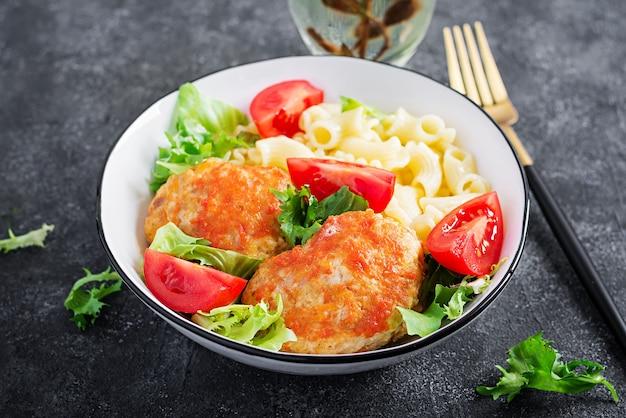 Creste di pasta e polpette di pollo al sugo di pomodoro.