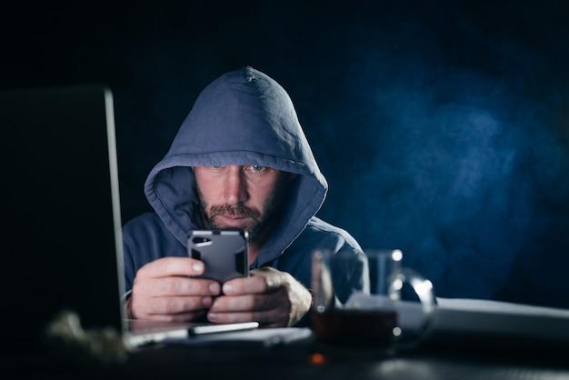 L'uomo pericoloso criminale in un cappuccio hackera lo smartphone, al buio
