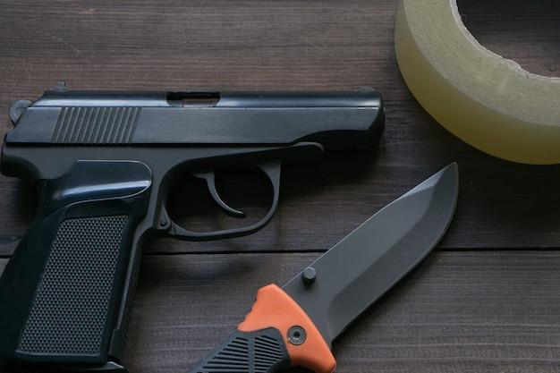 Apparecchiature per notizie criminali. pistola, coltello, nastro adesivo