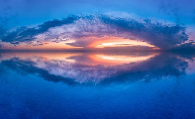 Il tramonto cremisi si riflette nell'acqua del lago, un bellissimo paesaggio estivo mattutino.