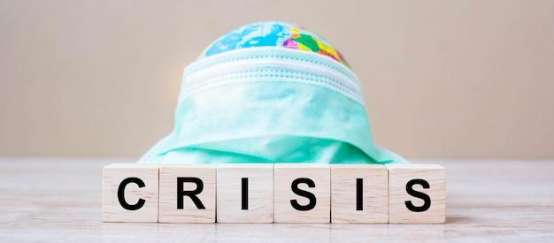 Cubetti di crisi con maschera e globo sullo sfondo della tabella.