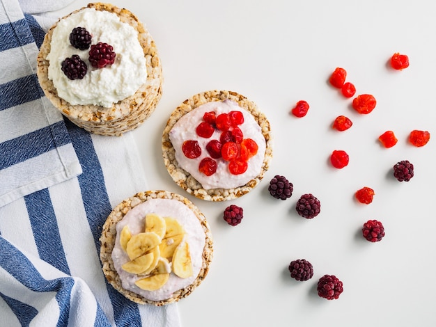 Fette biscottate, ricotta e frutta su un tavolo bianco. strofinaccio da cucina a righe.