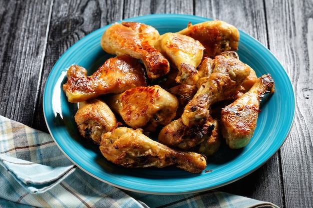 Cosce di pollo al forno croccanti servite su un piatto blu su uno sfondo di legno scuro, vista dall'alto, primo piano close
