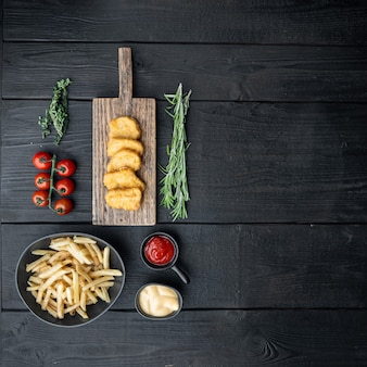 Carne di crocchette di pollo croccanti sul tavolo di legno nero
