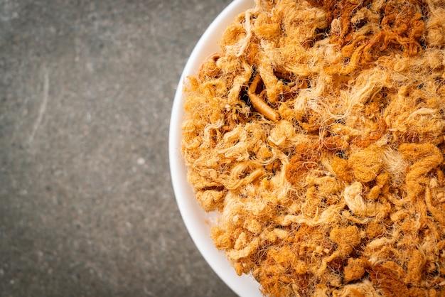 Rotolo di cocco croccante con maiale essiccato grattugiato sul piatto