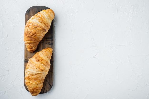Croissant freschi set di croissant, su pietra bianca sullo sfondo, vista dall'alto laici piatta, con copia spazio per il testo