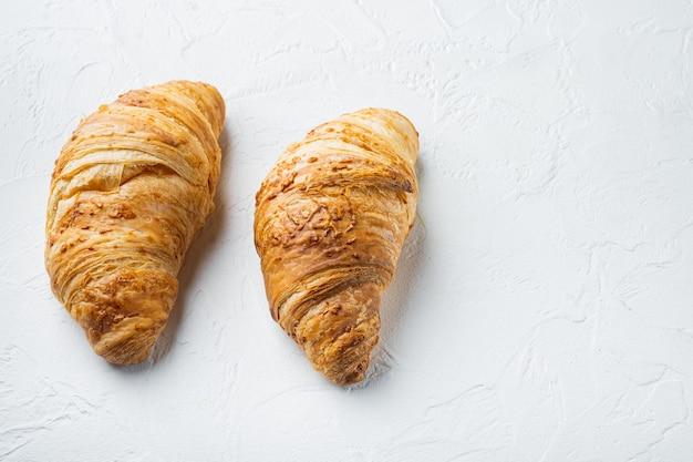 Set di croissant freschi croccanti, su sfondo di pietra bianca, con copia spazio per il testo