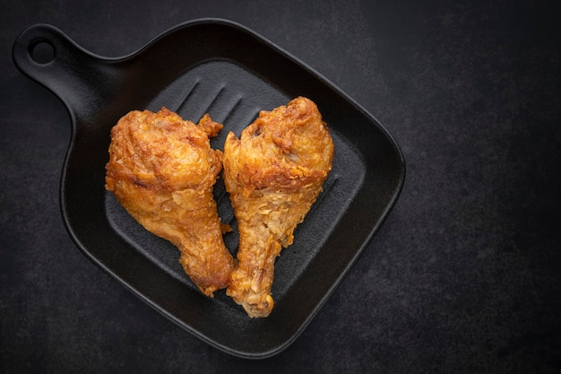 Coscia di pollo fritta croccante in padella nera su sfondo scuro, vista dall'alto