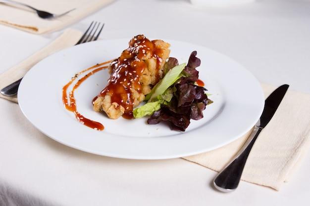 Piatto principale di pollo fritto croccante con salsa di verdure. preparato su piatto rotondo bianco al tavolo.