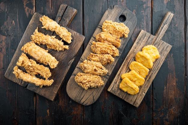 Parti croccanti del pollo fritto sulla vecchia tavola di legno scura, disposizione piana