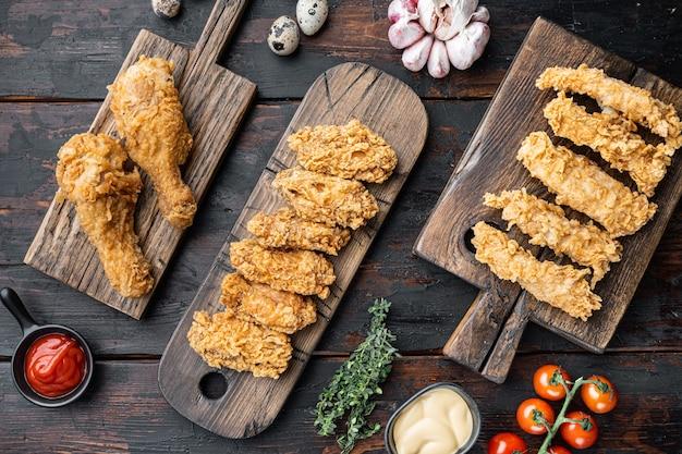 Croccanti parti di pollo fritto sul vecchio tavolo in legno scuro, piatto laici.