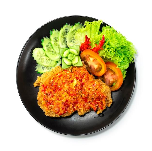 Pollo fritto croccante con salsa calda e piccante in un piatto nero isolato su fondo bianco