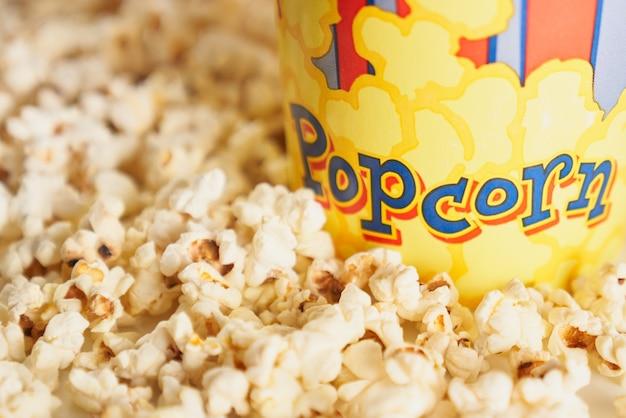 Popcorn fritto croccante vicino alla tazza di cartone. concetto di cinema.