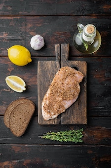 Ingrediente crudo di pollo croccante all'aglio, su tavola di legno, piatto