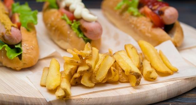 Patatine fritte dorate croccanti su una tavola di legno servite con baguette assortite con salsicce alla griglia e guarnizioni