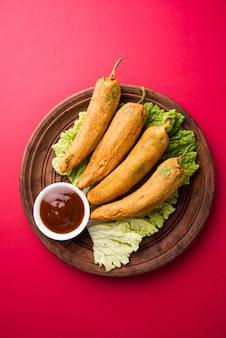 Pakora o mirchi bajji di peperoncino verde croccante, servito con ketchup su sfondo lunatico. è un popolare spuntino per l'ora del tè dall'india, specialmente nei monsoni. messa a fuoco selettiva