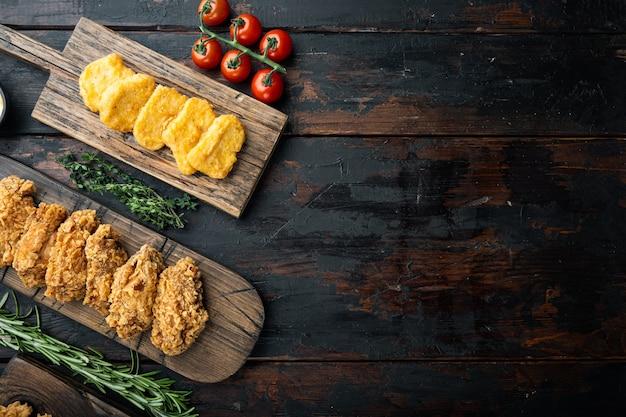 Tagli di pollo fritto croccante del kentucky sul tavolo di legno scuro, piatto laici.