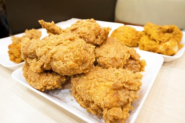 Pollo fritto kentucky croccante su un piatto bianco e tavolo.