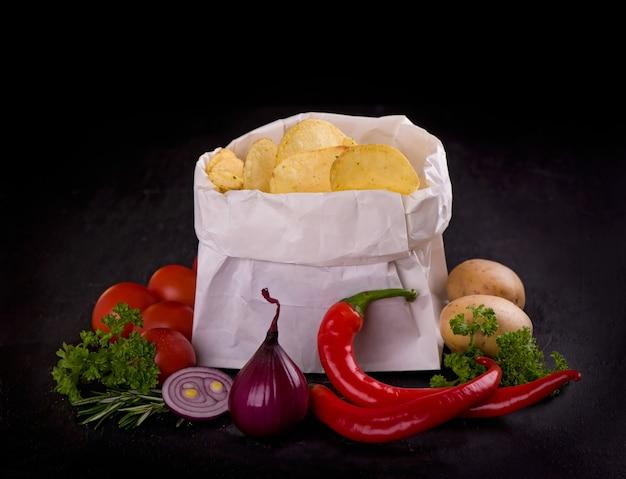 Patatine croccanti in un sacchetto sul tavolo scuro.
