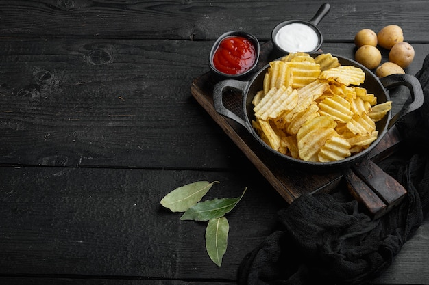 Patatine croccanti. fette di patate, arrostite con set di sale marino, su fondo di legno nero, con spazio di copia per il testo