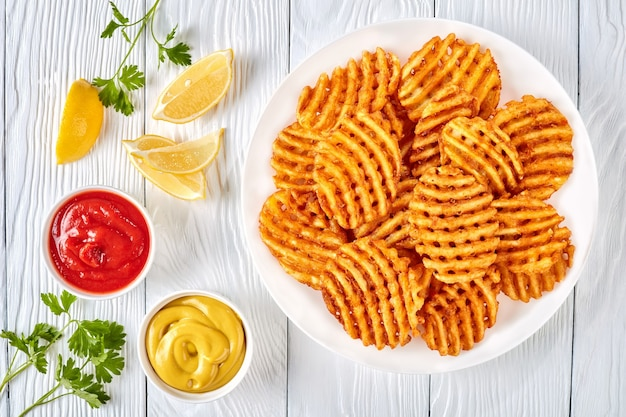 Cialde di patate croccanti patatine fritte, ondulate, crinkle cut, criss cross fries su una piastra bianca su una tavola di legno con senape e salsa di pomodoro immersione, vista da sopra, laici piatta