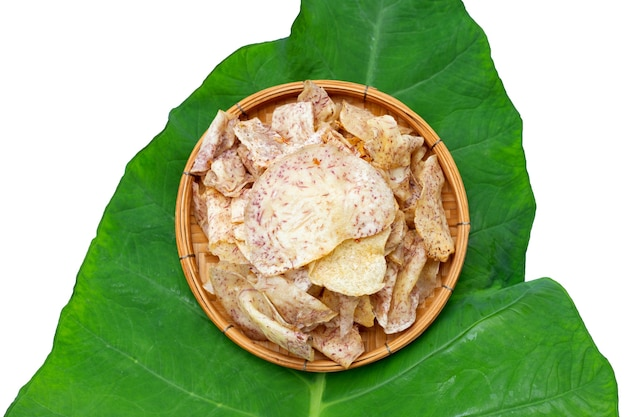 Chips di taro croccanti in cestino di bambù su foglia di taro