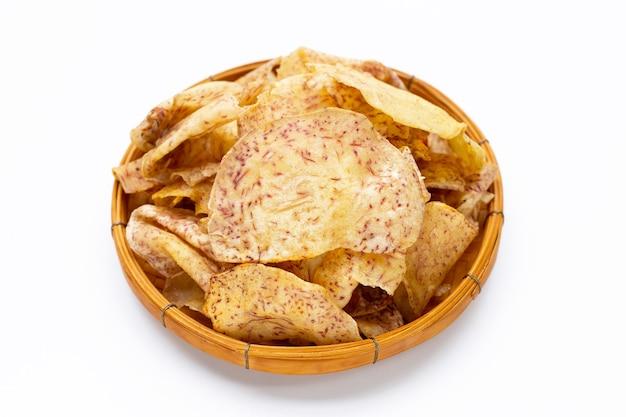 Chips di taro croccanti in cesto di bambù su sfondo bianco.