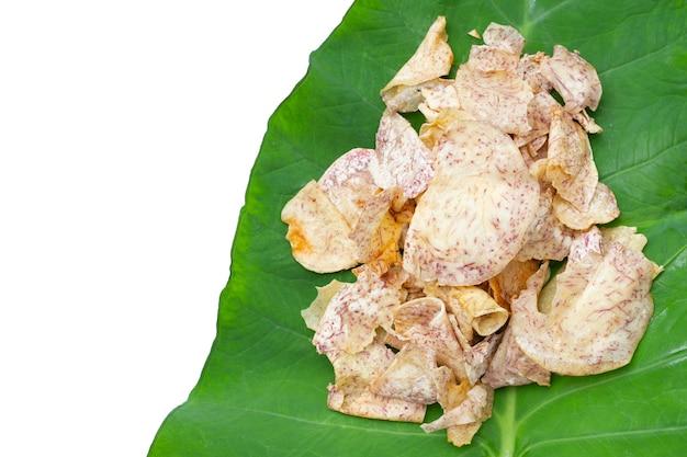 Chips di taro croccanti su foglia verde su sfondo bianco.
