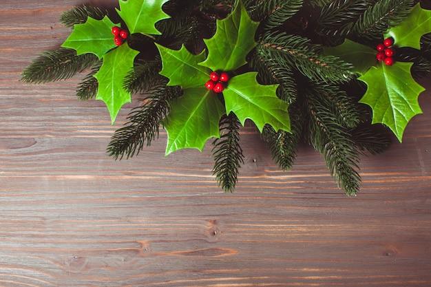 Natale bacca di agrifoglio e ramoscelli di abete sul grigio