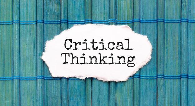 Testo di pensiero critico sul pezzo di carta sul legno verde